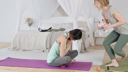 Instructor Giving Young Woman Water After Yoga Practice