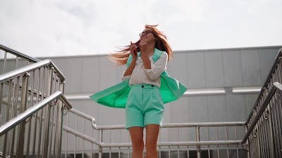 A beautiful slim woman in a trendy turquoise suit is spinning with happiness