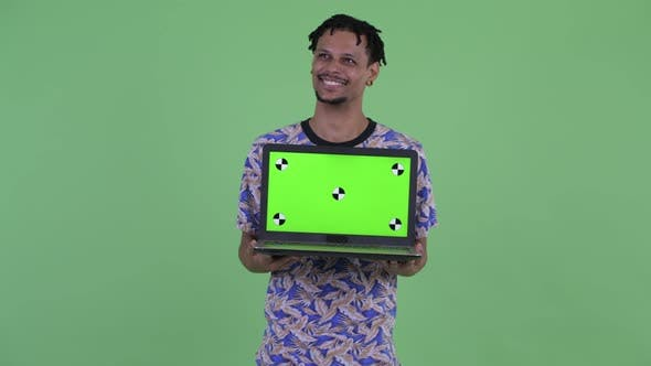 Thumbnail for Happy Young Handsome African Man Thinking While Showing Laptop