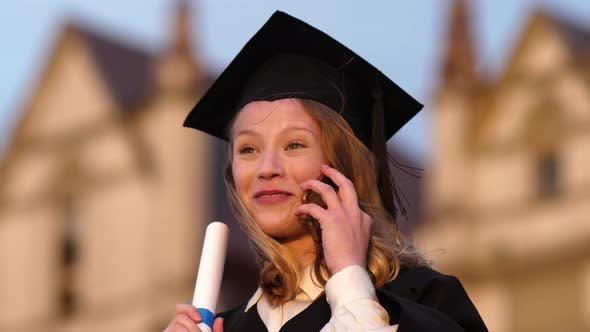Thumbnail for Happy Pretty Girl Graduate in Gown Talking on Mobile Phone
