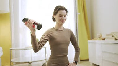 A Sporty Woman is Making an Exercise with a Bottle