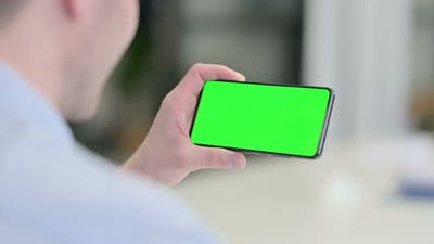 Rear View of Young Man Looking at Smartphone with Chroma Screen