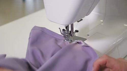 Seamstress Works at Sewing Machine Makes Straight Seams on Cloth Hands Closeup