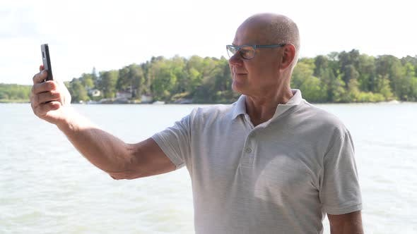 Thumbnail for Happy Senior Man Taking Selfie With Phone By The Lake
