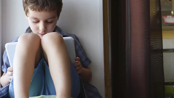 Thumbnail for Cute Little Boy Uses A White Tablet Pc On A Windowsill At Home