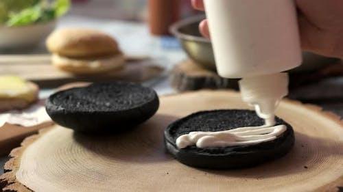 Geschnittenes schwarzes Brötchen und Sauce