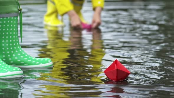 Cover Image for Girl Putting Paper Boat in Puddle