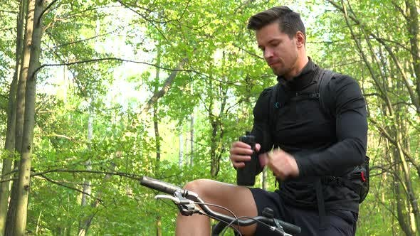 Thumbnail for A Cyclist Drinks From a Bottle in a Forest, Then Rides on - View From Below
