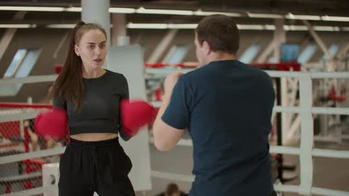 Boxing Training  an Attractive Woman Having a Training with a Boxing Coach  Learning How To Defense