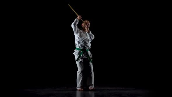 Thumbnail for Kendo Fighter on White Kimono Practicing Martial Art with the Bamboo Bokken on Black Background