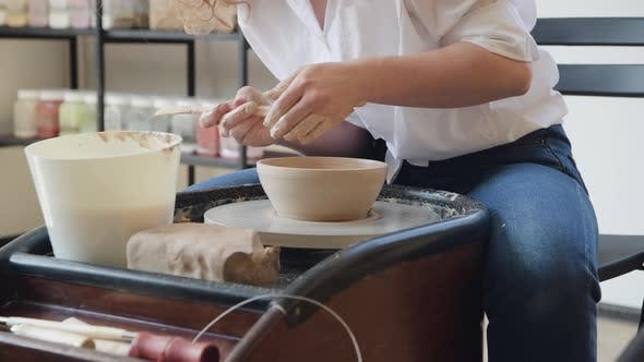 Potter Makes the Clay Product with Pottery Modeling Tools on the Potter's Wheel.