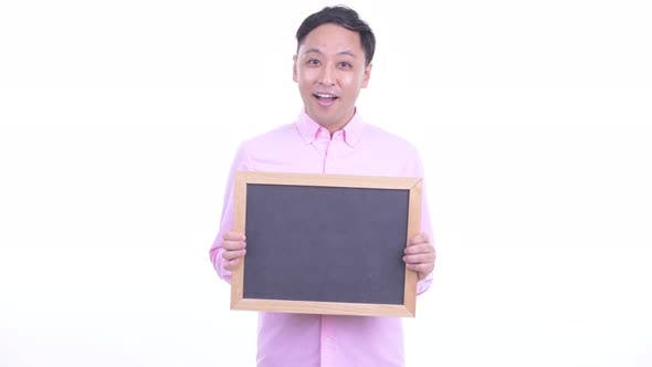 Thumbnail for Happy Japanese Businessman Talking While Holding Blackboard