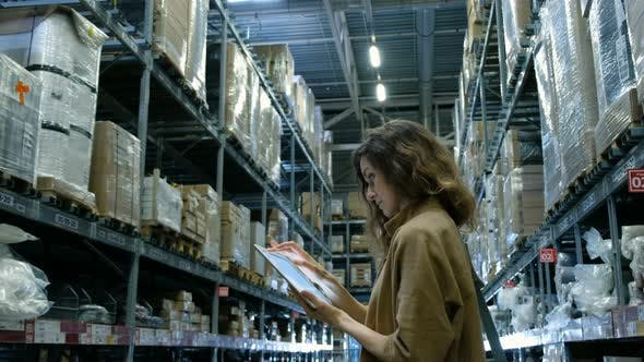 Thumbnail for Woman Uses a Tablet Computer Pc Looking in a Storage Room