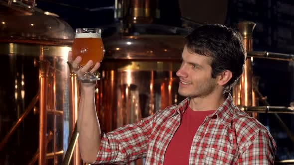 Thumbnail for Cheerful Male Brewer Smiling To the Camera, Examining Beer in a Glass