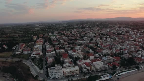Thumbnail for - Flying Over the Houses Rooftops in Coastal Town, Sunrise Scene. Nea Kallikratia, Greece
