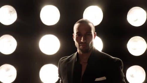 Hübscher und stilvoller Mann vor einer Lichterwand