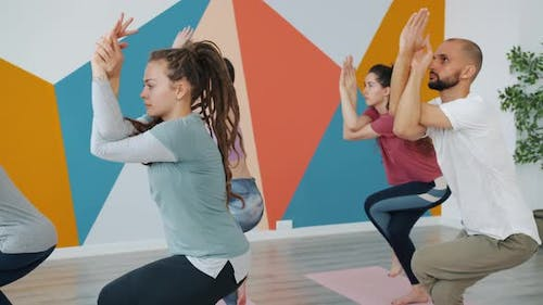 Girls and Guy Practising Eagle Position During Yoga Class in Modern Sports Center