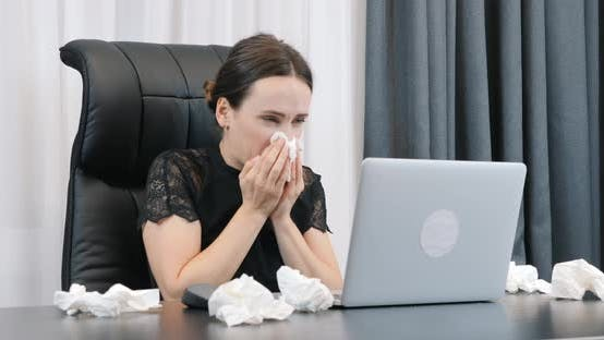 Thumbnail for Sick woman with runny nose working in office with dirty paper napkins lying around