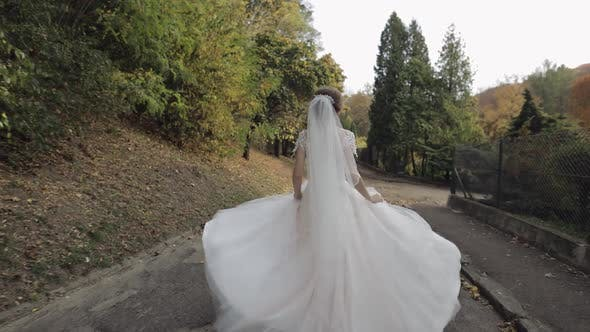 Thumbnail for Beautiful and Lovely Bride in Wedding Dress Running in the Park. Slow Motion