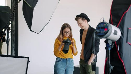 Model and Photographer Watching Photos on Camera After Photo Session in Studio
