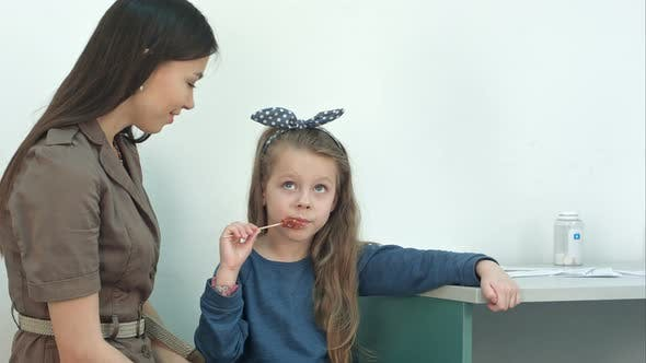 Thumbnail for Mother Talking To Her Little Girl Eating a Lollipop at Doctor's Office