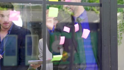 Group business meeting sticky post it colorful paper on mirror glass board to brainstorming discuss