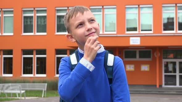 Thumbnail for A Young Boy Thinks About Something - an Elementary School in the Background
