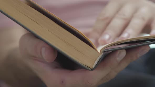 Thumbnail for Male Hands Leafing Through the Pages of the Book Indoors Close-up. Concept of Knowledge, Education