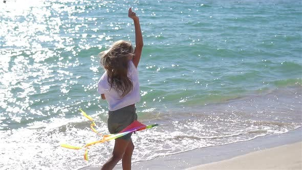 Little Girl Flying a Kite on Beach at Sunset