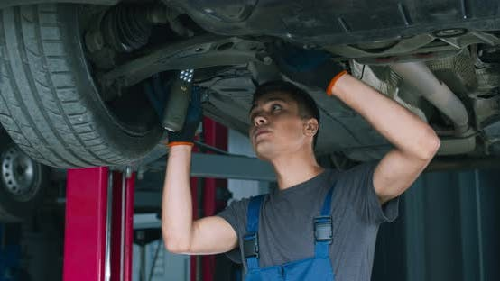 Thumbnail for Young Male Mechanic Repairing Car Suspension, Standing Under Vehicle at Garage