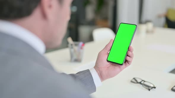 Businessman Looking at Smartphone with Green Chroma Key Screen