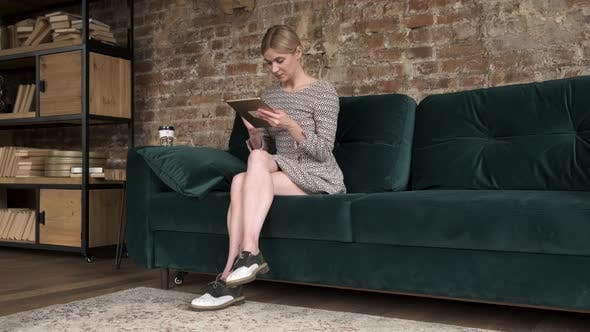 Thumbnail for Woman using tablet in home sofa in her living room. Happy female use tablet for texting, reading