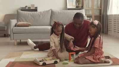 Father and Daughters Playing with Toys