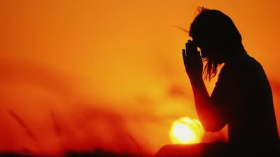 Profile of a Woman in Prayer at Sunset