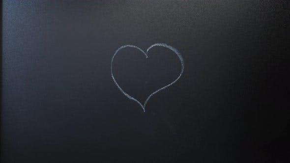 Hand draws heart icon on chalkboard