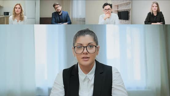 Serious lady in glasses talks to bored corporate colleagues