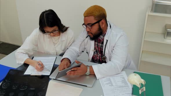 Thumbnail for Male Doctor Showing His Female Trainee How To Fill in Forms Using Tablet