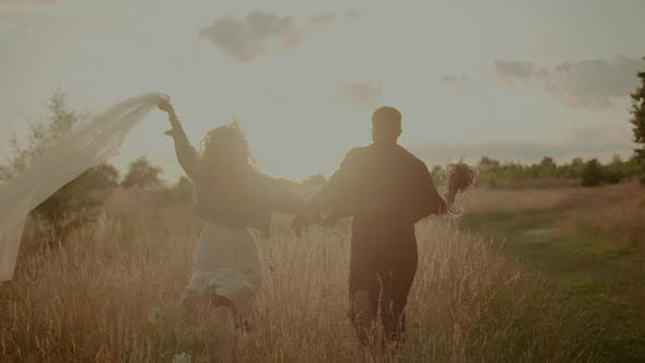 Carefree Young Couple Walking and Smiling on Holiday on Countryside  Freedom and Happiness Concept