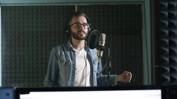 Thumbnail for Man Singing into Microphone in Recording Studio