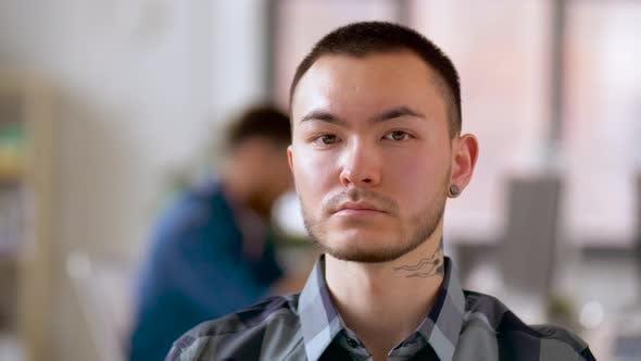 Thumbnail for asiatischer Mann mit Tattoo und Ohrtunnel im Büro
