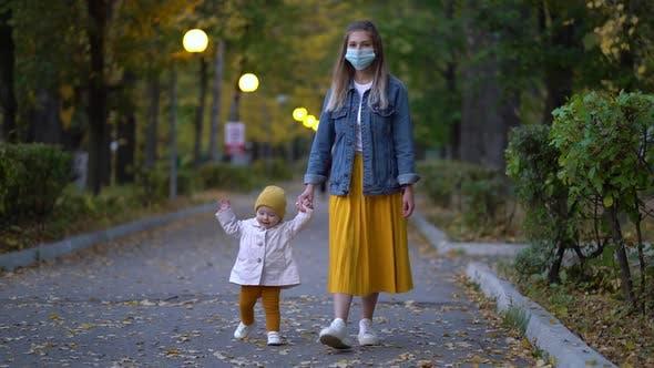 Thumbnail for Masked Mother Holds Hand Lovely Daughter on Street Walk During Second Wave Quarantine Coronavirus