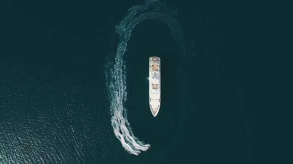 Top-down view of two jet-ski moving parallel to the large yacht. Super yacht