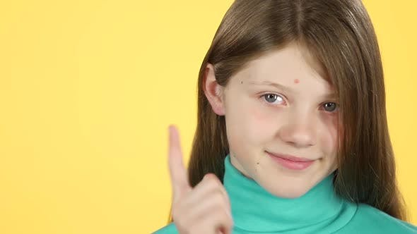 Cover Image for Close-up Girl Showing Emotion Punishment on Yellow Background. Slow Motion