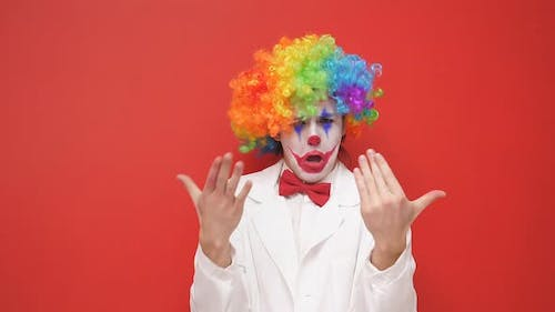 A Happy Clown Grimaces in Front of the Camera on an Isolated Background