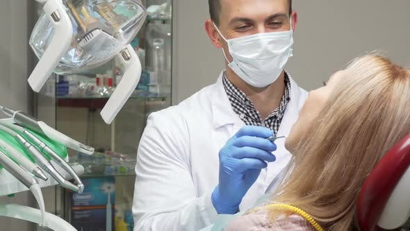 Thumbnail for Male Dentist Wearing Medical Mask Examining Teeth of Female Patient