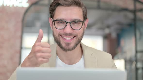 Thumbs Up By Young Man with Laptop