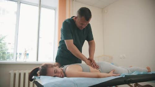 Woman Having an Osteopathic Treatment - the Doctor Massaging the Back