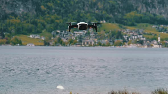 Thumbnail for Drone with Rotating Propellers Hanging in the Air on a Background of Lake and Mountains
