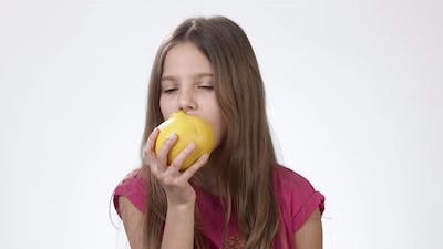 Girl with an Apple. Little Girl Eats a Big Yellow Apple on a White Background.