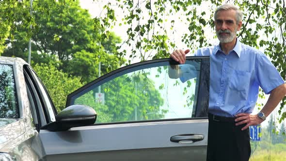 Thumbnail for Senior Man Stands Next To the Car, Looks Around and To the Camera (Car Stands on the Verge of Road)